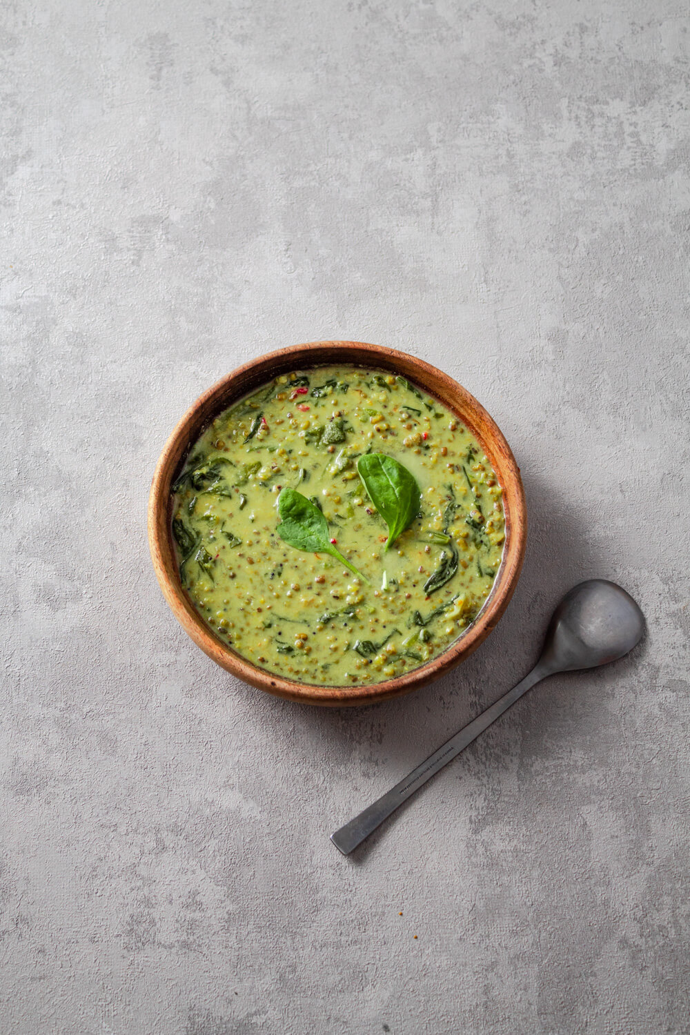 Mung bean and spinach curry in a bowl with a garnish of spinach leaves.