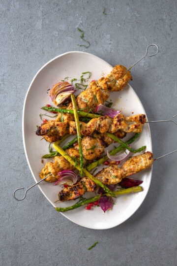 Chargrilled Chicken Kebabs Garnished with Asparagus, Roasted Red Onions, Pomegrante and Mint on a Large Serving Platter
