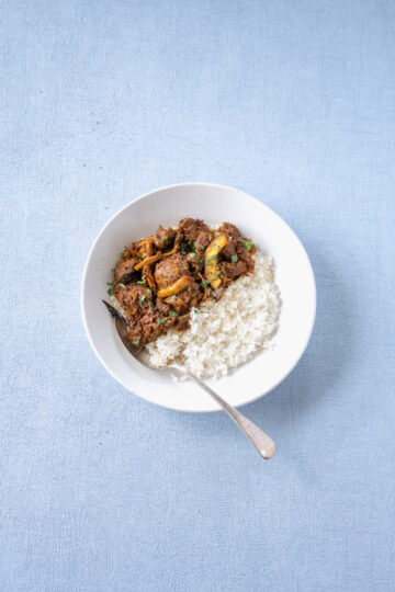 Dry fried lamb curry with white rice in a bowl