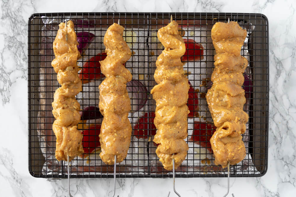 Chargrilled Chicken Kebabs - Skewering the Chicken and Laying the Skewers on Baking Tray
